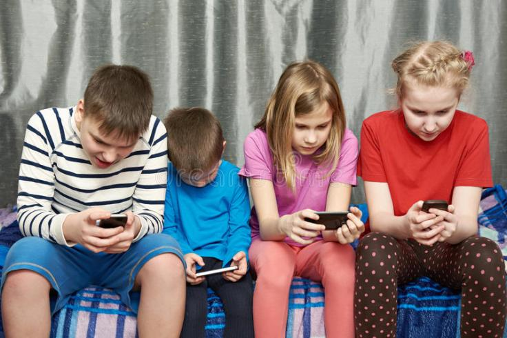 children-playing-game-mobile-phones-home-50113780